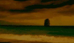 Barco navegando cerca de la costa al anochecer